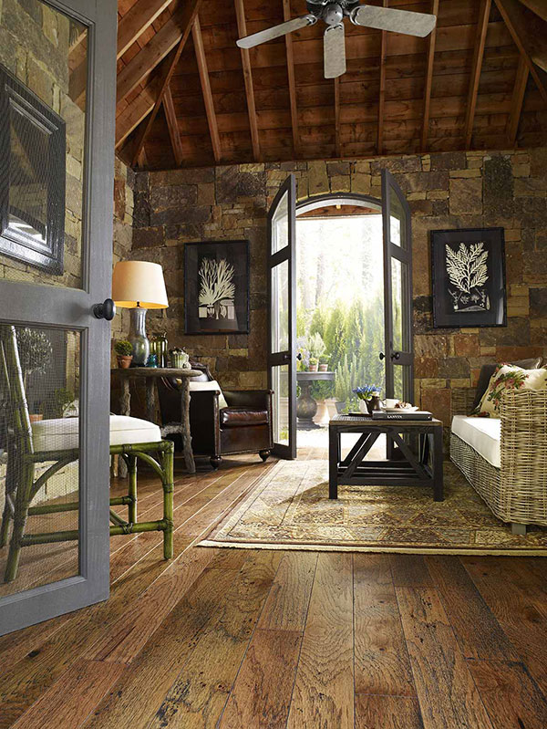 Living room inside a rustic cabin with a wicker couch and area rug on the wood floor